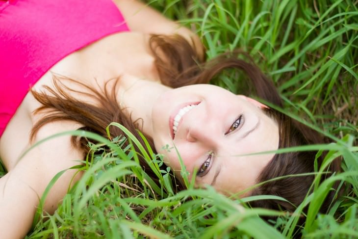 דרכים להגברת רמות הסרוטונין: אישה שוכבת על הדשא ומחייכת