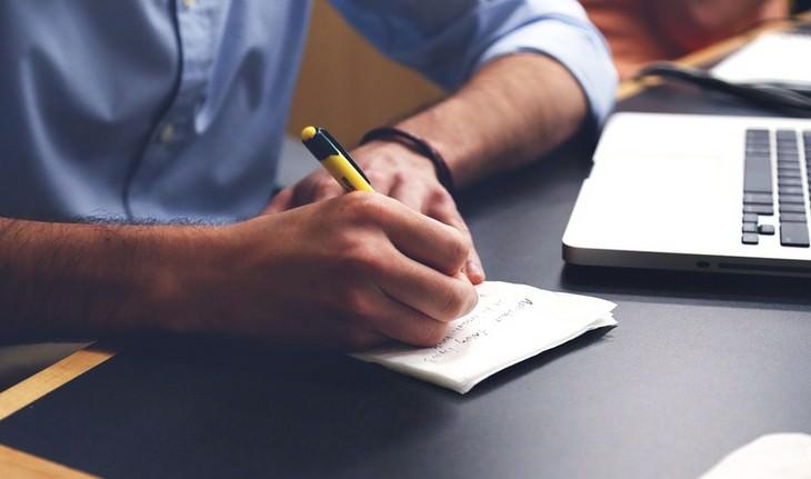 10 חוקים להצלחה: יד של גבר כותבת על נייר לצד מחשב נייד