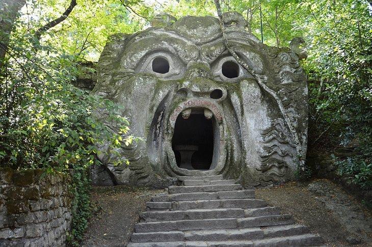 דמות מפלצת חצובה באבן, סביב צמחייה