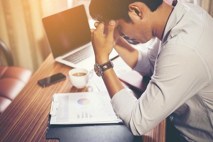 גבר מניח את ידיו על הרקות שלו לצד שולחן עבודה