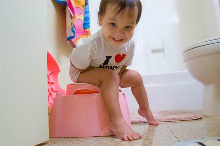 מדריך לגמילת ילדים מחיתולים: ילד יושב על סיר לילה ומחייך