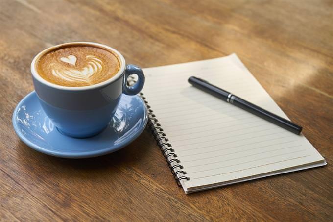כוס קפה לצד מחברת ועט
