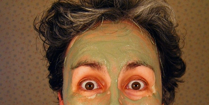 אישה עם מסכת חימר ירוק עליה