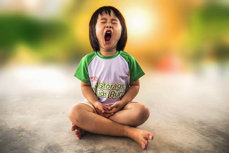טעויות שהורים עושים בחינוך ילדיהם: ילדה יושבת בשיכול רגליים ומפהקת