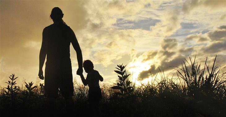 צללית של אב וילד קטן הולכים יד ביד בין צמחייה