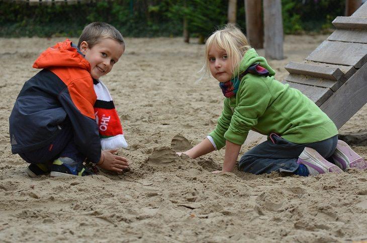 חוקי משמעת מפתיעים ויעילים לילדים: ילד וילדה משחקים בחול
