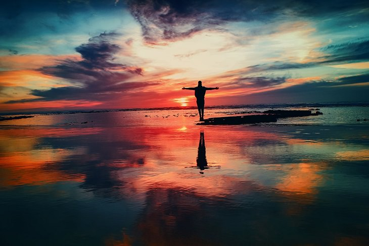 איש עומד על סלע באמצע הים ופורש ידיים