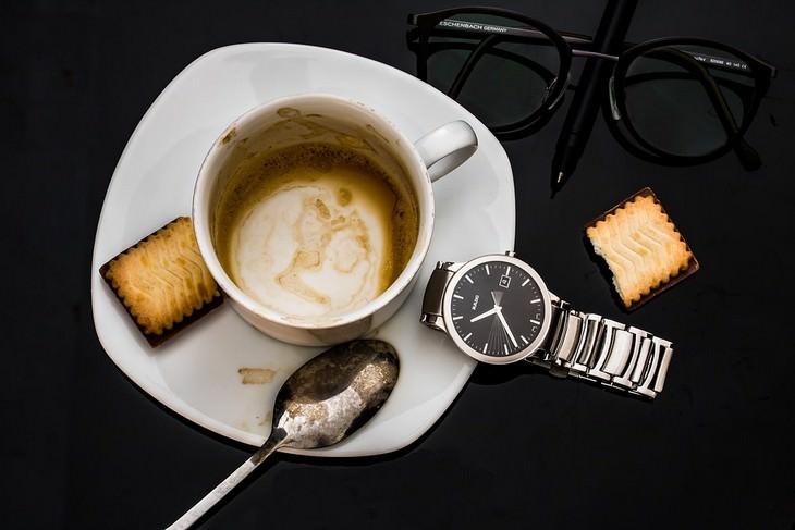 כוס קפה על צלחת עם שעון, משקפיים וביסקוויטים לידה