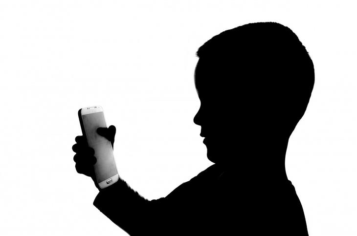 צללית של ילד משתמש בסמארטפון