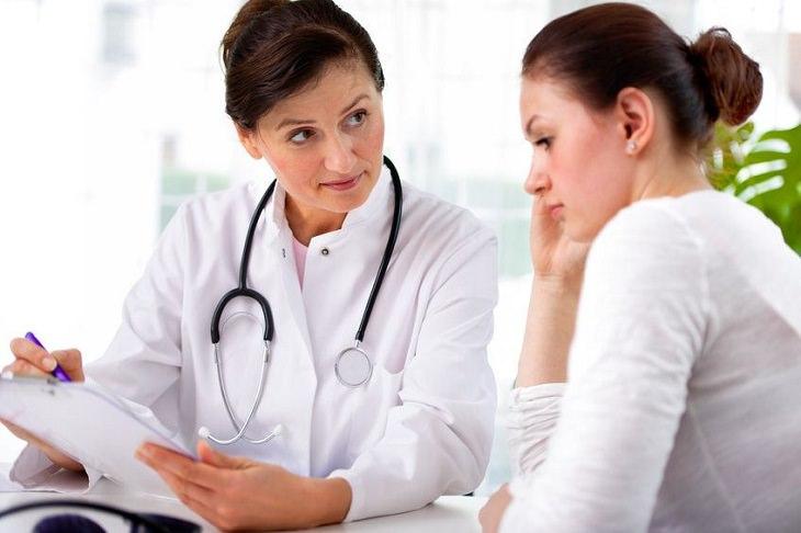 אישה מעיינת במסמכים רפואיים עם רופאה