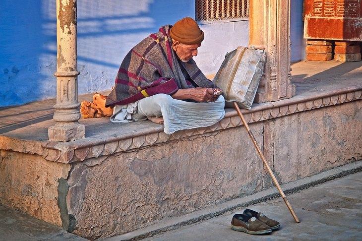 איש מבוגר יושב בבגדים בלויים ברחוב