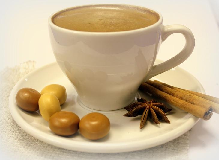 יתרונות הקפה הלבן: כוס קפה לצד קינמון, כוכב אניס וסוכריות