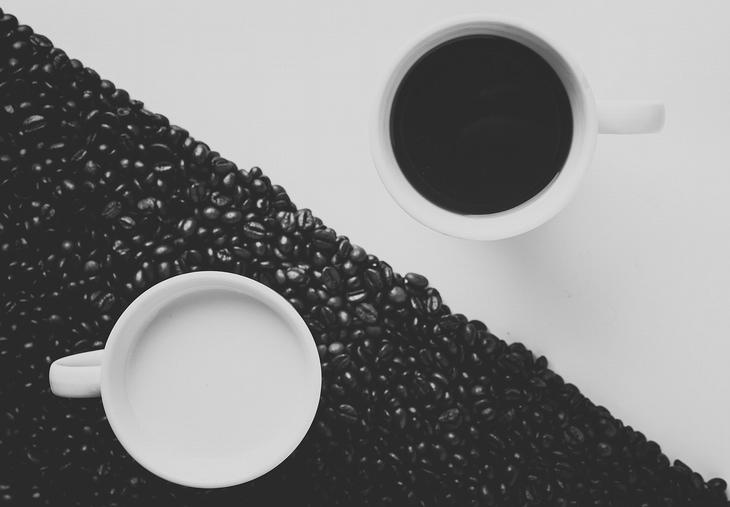 יתרונות הקפה הלבן: כוס קפה שחור על רקע לבן, לצד כוס עם חלב על פולי קפה