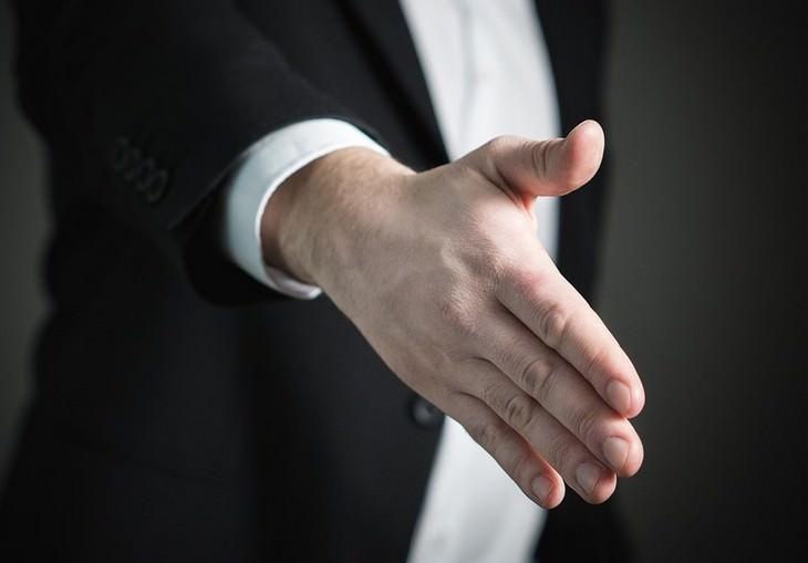 יד של גבר לבוש חליפה מושטת קדימה