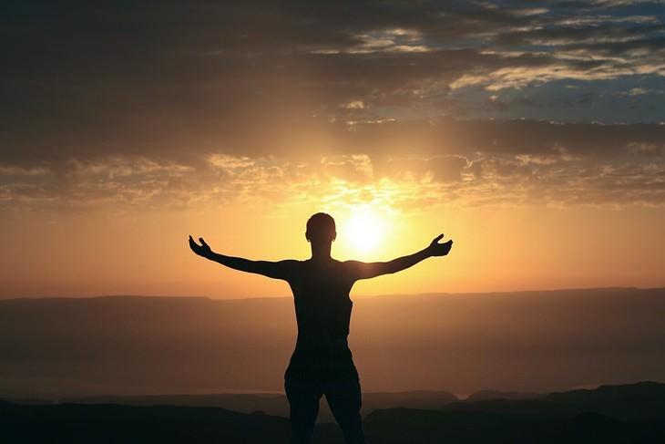 צללית של אדם עומד עם ידיים פרושות לצדדים מול שקיעה