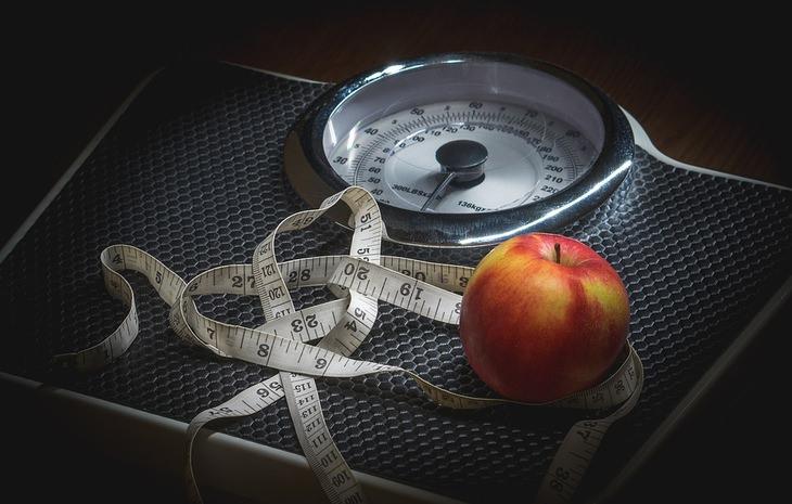 סימנים לתת פעילות של בלוטת התריס: משקל עליו מונחים סרט מדידה ותפוח