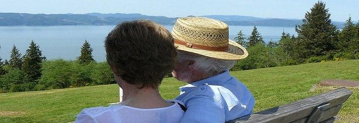 מידע על אגודת רעות אשל: זוג מבוגר יושב על ספסל במדשאה מול הים