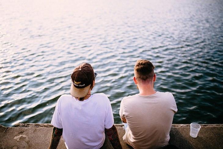 שני גברים יושבים על מזח בגבם למצלמה