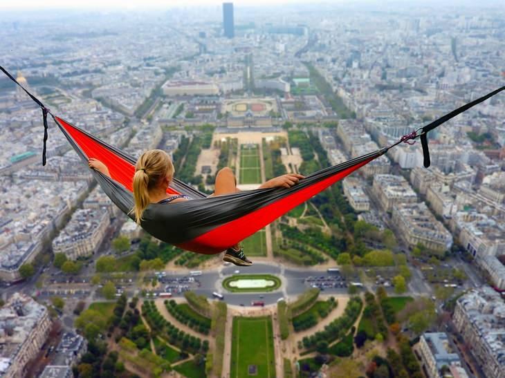 אישה שוכבת על ערסל בגובה רב, מעל נוף עיר
