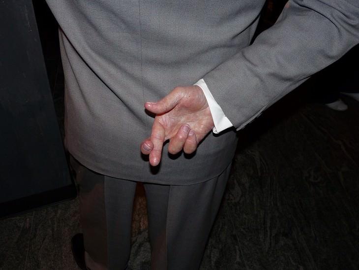 יד של גבר מצליבה אצבעות מאחוריי גבו