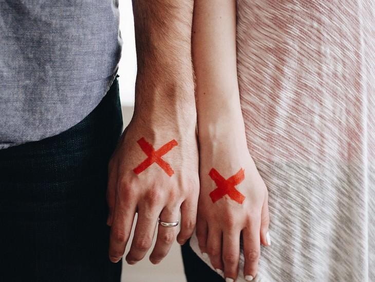 ידיים של גבר ואישה מונחות זו לצד זו עם סימן של איקס עליהן