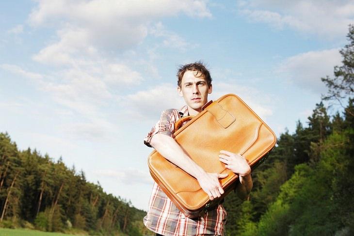 גבר עם מבט מוטרד אוחז מזוודה סמוך לחורשה