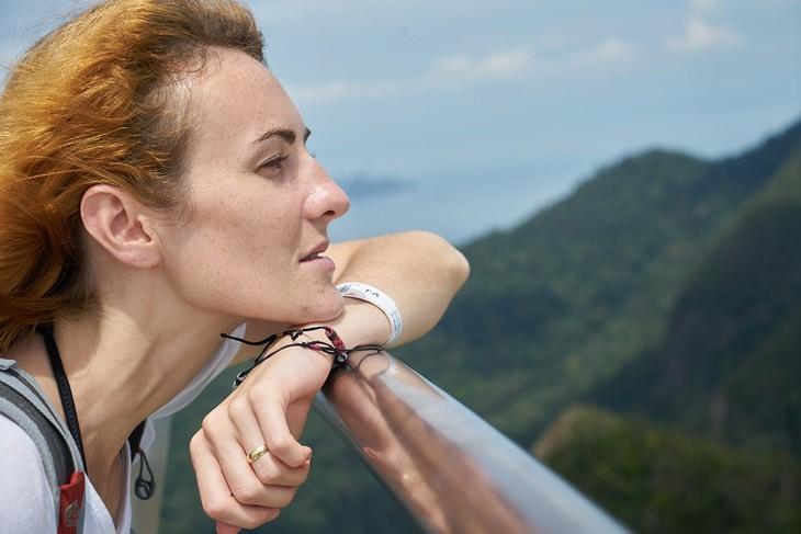 אישה נשענת על מעקה ומביטה לנוף טבעי באופק