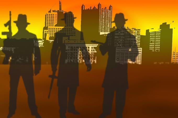 צלליות של אנשי מאפיה מול רקע עירוני