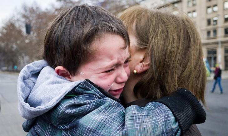 איך להתמודד עם כעס אצל ילדים: ילד בוכה מחבק אישה