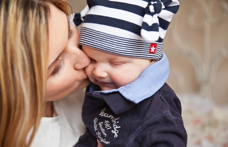 טיפים להקלה על כאבי בקיעת שיניים: אימא נושקת לתינוק שלה