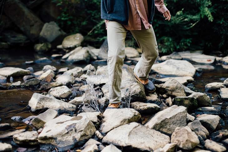 מניעת התכווצויות בשרירי הרגליים: איש הולך על סלעים בטבע