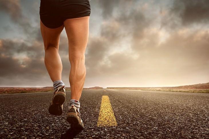 מניעת התכווצויות בשרירי הרגליים: איש עם רגליים שריריות רץ על כביש