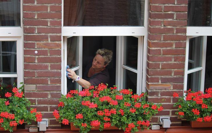 אישה מנקה חלון זכוכית