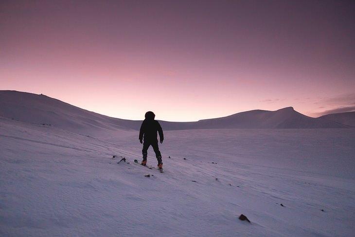 גולש סקי עומד לבדו מול הרים מושלגים