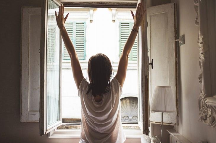 אישה עומדת עם ידיים למעלה מול חלון עם אור יום