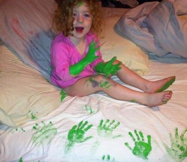 ילדה עם ידיים וזרועות צבועות יושבת על סדין עם כתמים בצורת היד שלה
