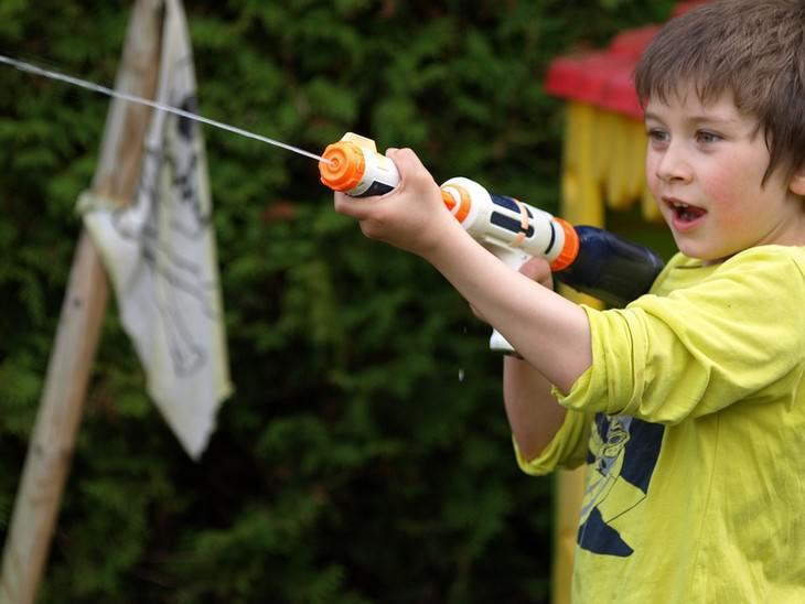 ילד יורה באקדח מים