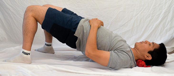 נקודות לחיצה לטיפול בכאבי גב: איש שוכב עם צווארו על גרב שבתוכה שני כדורי טניס