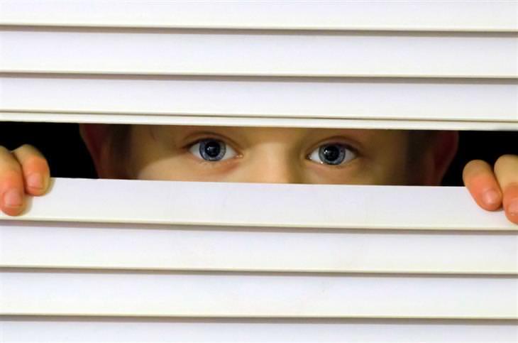 טיפים להורים של ילדים ביישנים ומופנמים: ילד מסתתר מאחורי שלבי חלון ורואים רק את עיניו