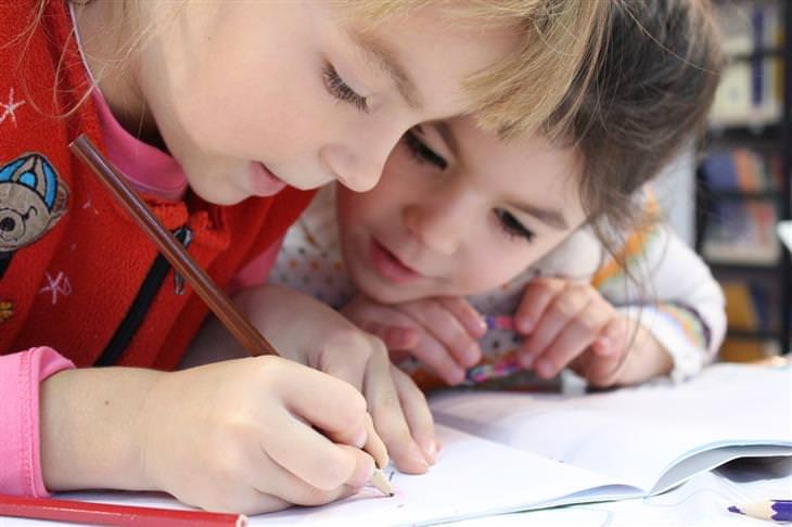 טיפים להורים של ילדים ביישנים ומופנמים: ילדה כותבת במחברת וילדה אחרת מסתכלת עליה בעניין רב