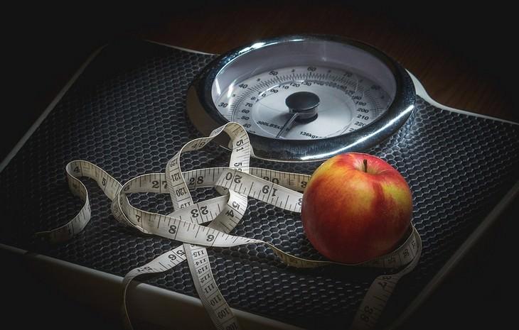 מאכלים שמשבשים חילוף חומרים: משקל עם תפוח וסרט מדידה עליו