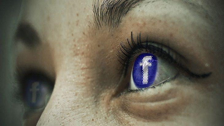 הדבקה רגשית: תקריב על אישוני עיניים עם סמל פייסבוק עליהם