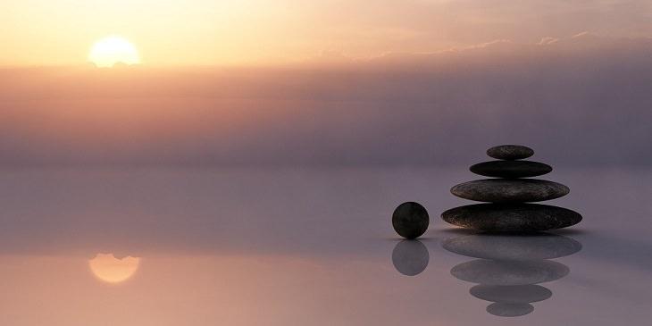 תרגיל חמשת הטיבטים: אבנים מונחות זו על זה עם שקיעה ברקע