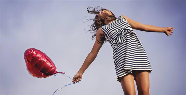 הזכויות שנולדנו איתן: אישה מחזיקה בלון בצורת לב ומחייכת לשמים