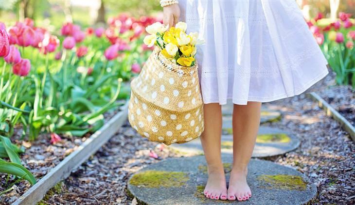הזכויות שנולדנו איתן: אישה עומדת יחפה על שביל בגינה ומחזיקה בידה סלסלה עם פרחים