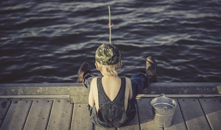 תחביבים שתורמים לבריאות: ילד דג על מזח