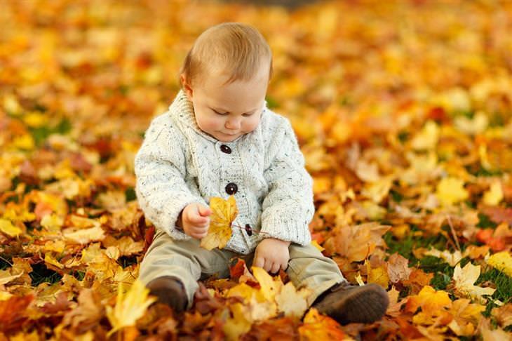 מצבים שמסכנים ילדים במגע עם חיידקים: ילד יושב על עלי שלכת ומשחק איתם