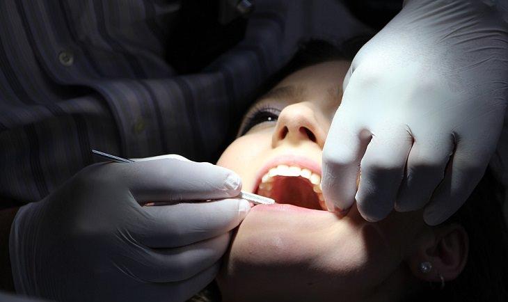חידושי רפואת שיניים: אישה פותחת פה בזמן שרופא שיניים בוחן אותו