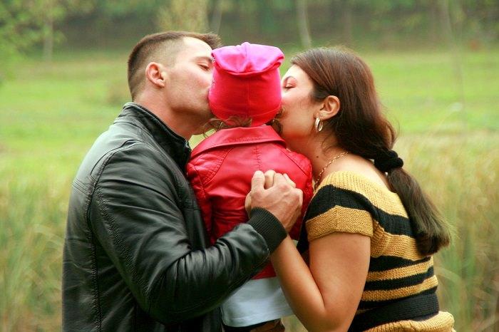 אמא ואבא מנשקים ילדה על הלחי