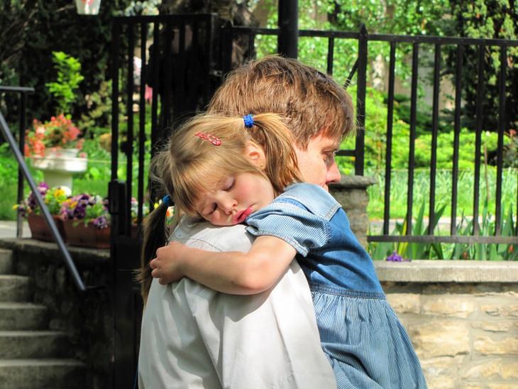 אב מחזיק את בתו הרדומה בזרועותיו